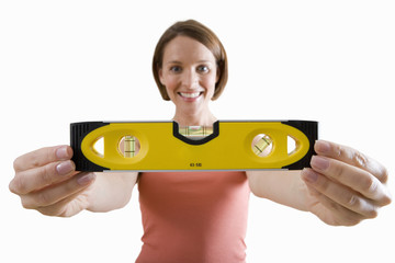 young woman holding spirit level, cut out