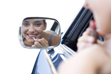 girl putting on lipstick in car mirror, cut out