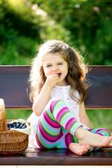 little girl eating blueberries outdoors