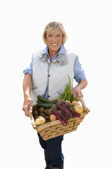 senior woman holding basket of vegetables, cut out