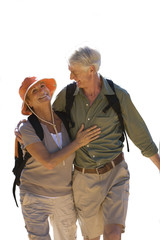 senior couple with rucksacks walking, cut out