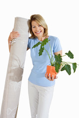 woman holding house plant and rolled carpet, cut out