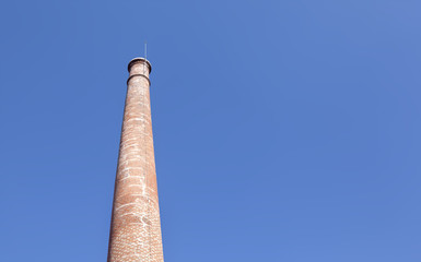Old brick chimney against blue sky
