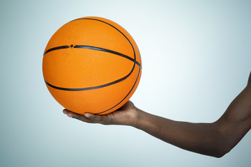 Hand holding a basket ball on gray background