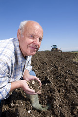 Farmer cupping soil with tractor and plough in background