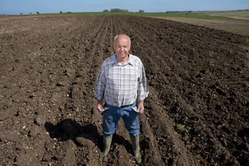 Farmer showing empty pockets in ploughed field