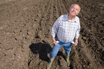 Farmer showing empty pockets and looking up in ploughed field