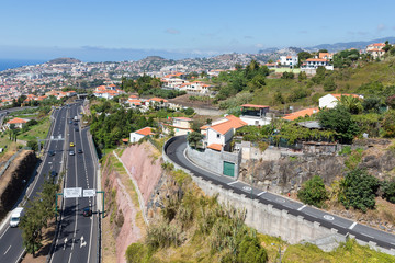 Aerial view of Funchal and highway, build against  mountains