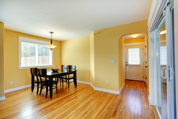 Bright yellow house interior. Dining area with wooden table and