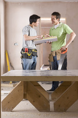Male carpenter and apprentice with tools talking next to sawhorse