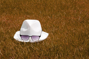 white hat and sunglasses dry grass on autumn