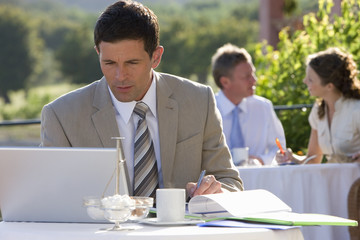 Businessman using laptop at cafŽ