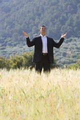 Businessman standing with arms outstretched in rural field
