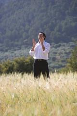 Businessman gesturing in rural field