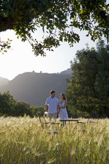 Couple carrying wine and holding hands near table in rural field
