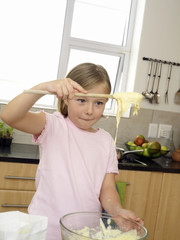 Girl (6-8) standing in kitchen, holding cake mix with wooden spoon above glass bowl