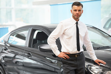 Salesman standing in car retail store. Car Showroom.