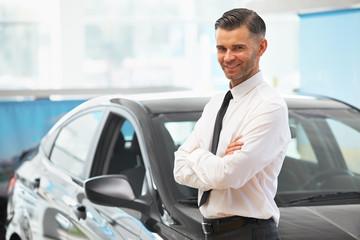 Salesman Stands Near Brand New Car. Car Showroom