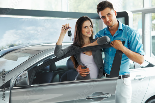 Young Couple Celebrating Purchase of a car In Car Showroom - 69333508