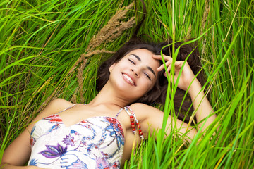 Young woman resting and day lying down on green grass