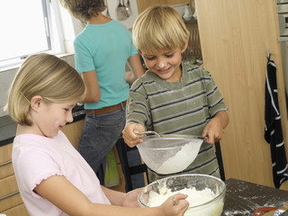 Boy (5-7) and girl (6-8) sieving flour into bowl, smiling, mother standing at kitchen sink (tilt)