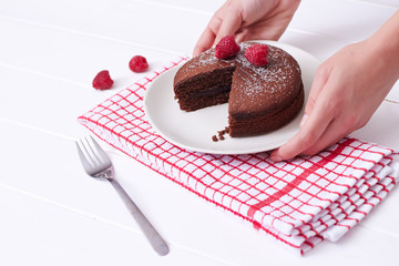 Chocolate sponge cake served on a white wooden table