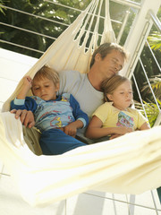 Father and children (5-8) relaxing in hammock on balcony, sleeping (tilt)