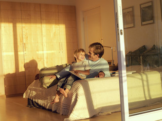 Father and son (5-7) sitting on bed, looking at photo album, view through open sliding doors