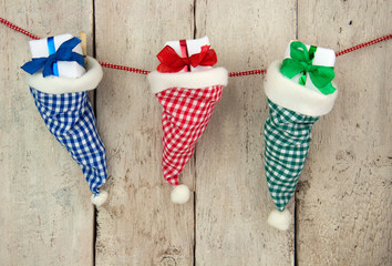 Three chequered santa hats with christmas gifts