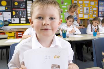 School boy displaying artwork in classroom