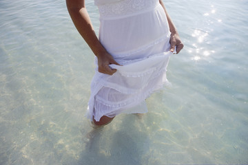 Woman in white dress standing on beach, ankle deep in sea water, low section