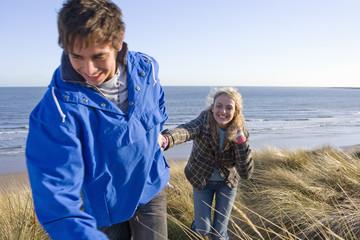 Couple walking on sand dune near ocean