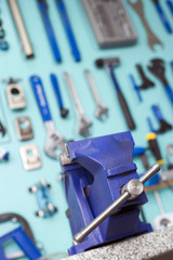 Blue vice in front of display rack in tool shop, focus on foreground, low angle view (tilt)