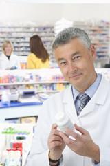 Pharmacist reading label on medicine bottle in pharmacy
