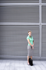Businesswoman in green short-sleeved blouse and grey skirt standing on pavement, portrait