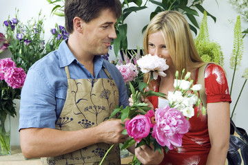 Blonde woman smelling flowers in flower shop, male florist looking on, smiling, side view