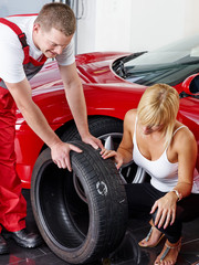 Customer and mechanic in a garage looking at a tire