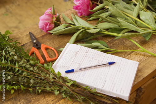 Pink flowers on table beside order pad and scissors in flower shop, close-up (still life)
