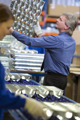 Manager inspecting trays of aluminium light fittings in factory