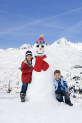 Portrait of happy boy and girl with snowman on mountain