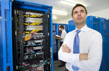 Businessman with arms crossed looking up pensively in network server room