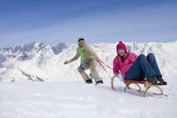 Man pulling woman up ski slope on sled