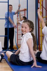 Gym teacher helping student climb gymnasium climbing equipment