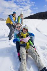 Parents on ski slope pulling children up hill on sled
