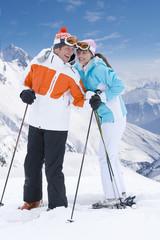 Skiers standing on mountain ski slope