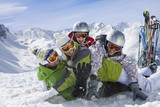 Fototapeta Skis in snow and family having snowball fight on mountain top