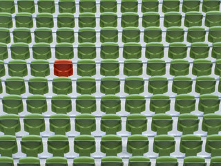 One red seat in rows of empty, green stadium seats