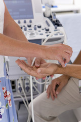Technician using ultrasound treatment on patient's wrist