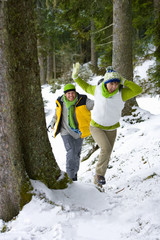 Couple having snowball fight together in woods