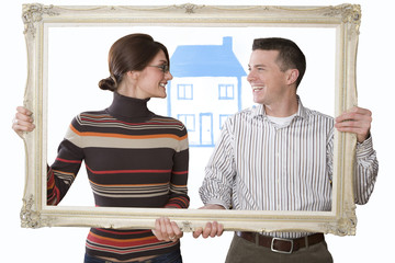 Smiling couple holding empty frame with house in background